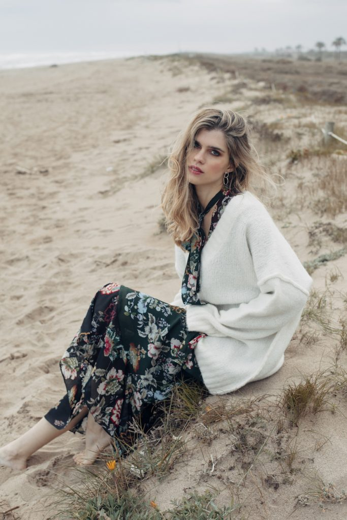 Modelo con vestido de flores en la playa sentada.