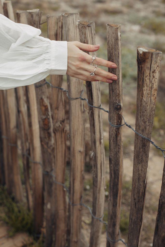 Detalle mano con vestido y blusa blanca boho y anillos de flores