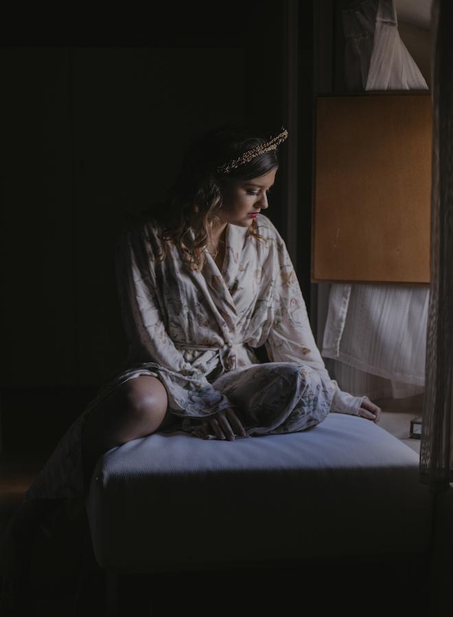 novia mirando por la ventana con el joyero y las alianzas de boda