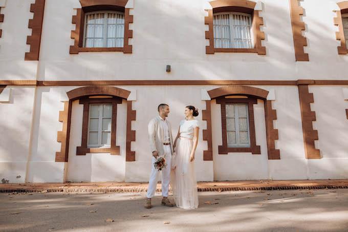novios con outfit en tos pastel en la fachada de la casa