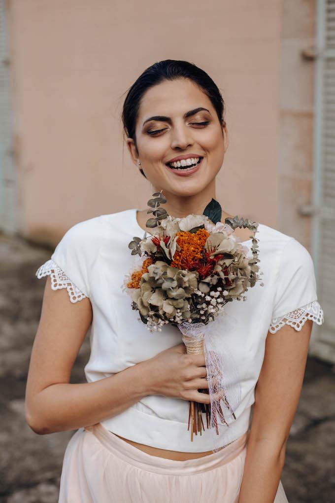 novia sonriendo con ramo y pendientes laia ossorio